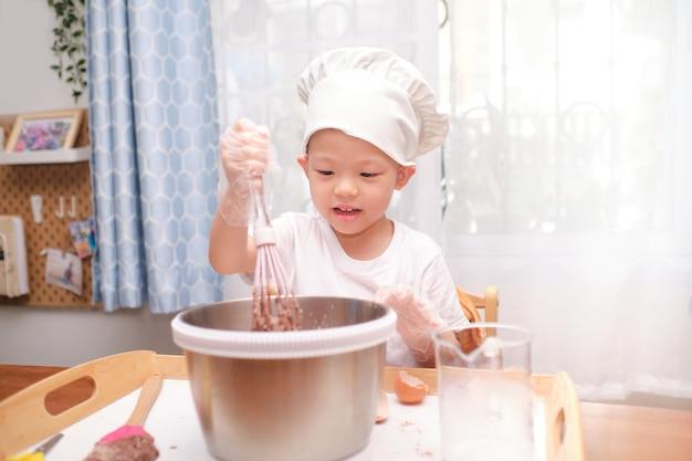 Mignon Enfant Garçon Asiatique De 4 Ans S'amusant à Préparer Des Gâteaux Ou Des Crêpes Profiter De La Pâte à Mélanger à L'aide D'un Fouet à La Maison Photo Premium