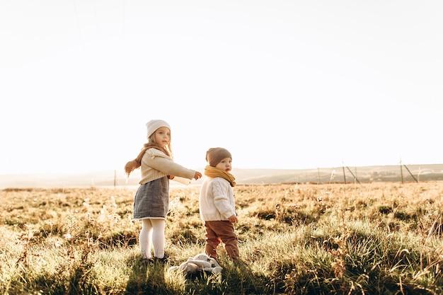 Un mignon enfants jouent dans le champ vert au coucher du soleil Photo Premium