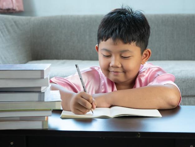 Mignon garçon asiatique écrire des devoirs à la maison. concept d'éducation Photo Premium