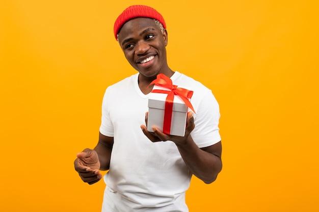 Mignon Homme Africain Noir Avec Un Sourire Dans Un T-shirt Blanc Tend Une Boîte Un Cadeau Avec Un Ruban Rouge Pour La Saint Valentin Sur Fond Jaune Photo Premium