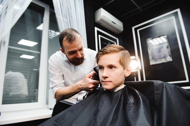 Un Mignon Jeune Garçon Se Coupe Les Cheveux Photo Premium