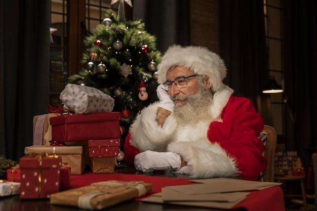 Mignon Père Noël à La Table En Pensant Photo gratuit