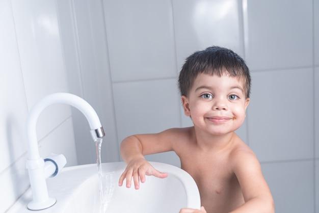 Mignon Petit Bébé Garçon Lavant La Main Dans Le Lavabo De La Salle De Bain Photo gratuit