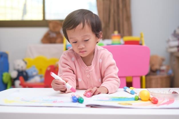 Mignon Petit Enfant Asiatique Bébé Fille Enfant à Colorier Avec Des Crayons à La Maison Photo Premium