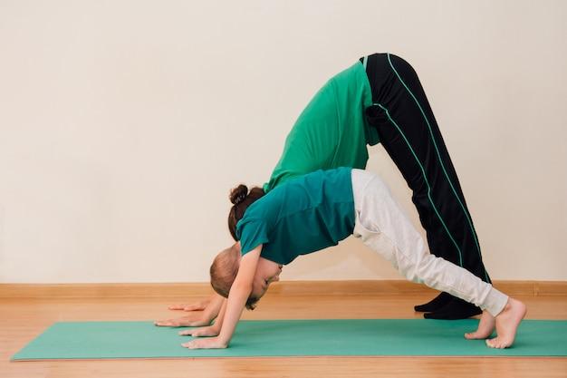 Un mignon petit garçon apprend à faire du yoga dans la salle de sport Photo Premium