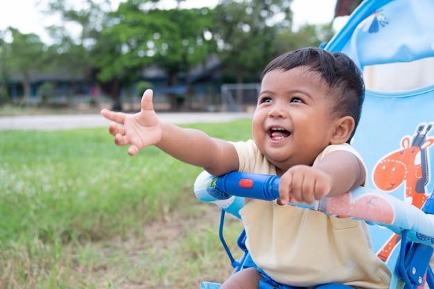 Mignon petit garçon asiatique assis sur une poussette Photo Premium