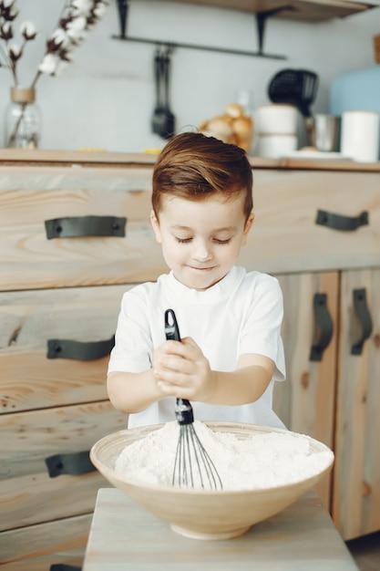 Mignon petit garçon assis dans une cuisine Photo gratuit