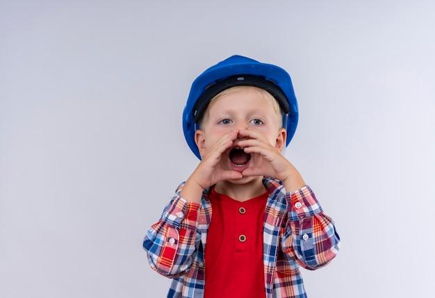 Un Mignon Petit Garçon Aux Cheveux Blonds Portant Chemise à Carreaux En Casque Bleu Appelant Quelqu'un Avec Les Mains Sur La Bouche Sur Un Mur Blanc Photo gratuit