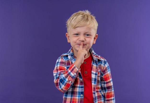 Un Mignon Petit Garçon Aux Cheveux Blonds Portant Une Chemise à Carreaux En Gardant L'index Sur Sa Bouche Exprimant Le Geste Chut Sur Un Mur Violet Photo gratuit