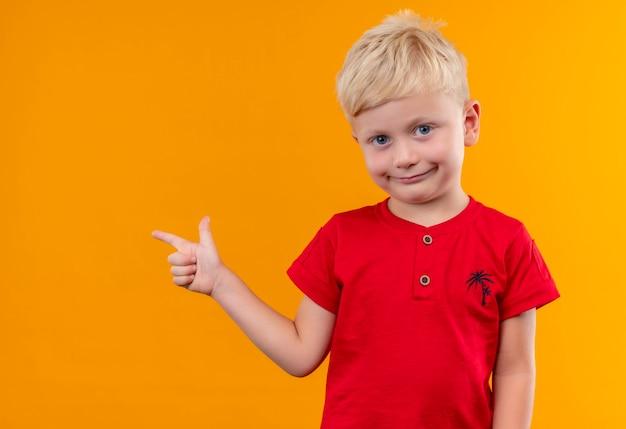 Un Mignon Petit Garçon Aux Cheveux Blonds Portant Un T-shirt Rouge Montrant Quelque Chose Avec L'index à La Recherche Sur Un Mur Jaune Photo gratuit