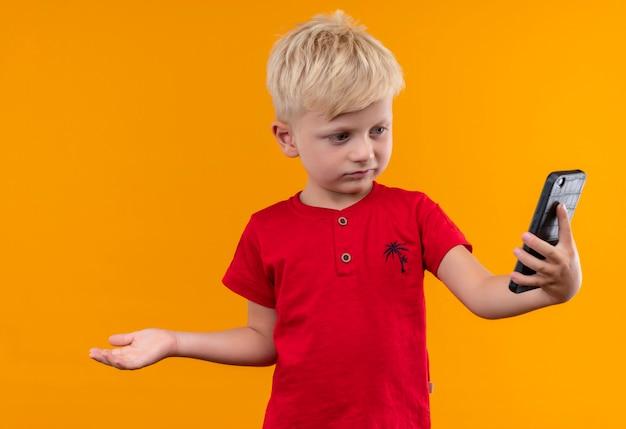 Un Mignon Petit Garçon Aux Cheveux Blonds Portant Un T-shirt Rouge à La Recherche De Téléphone Mobile Avec La Main Ouverte Sur Un Mur Jaune Photo gratuit
