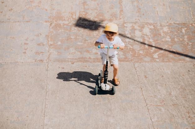 Mignon Petit Garçon Aux Cheveux Bouclés équitation Scooter Photo gratuit