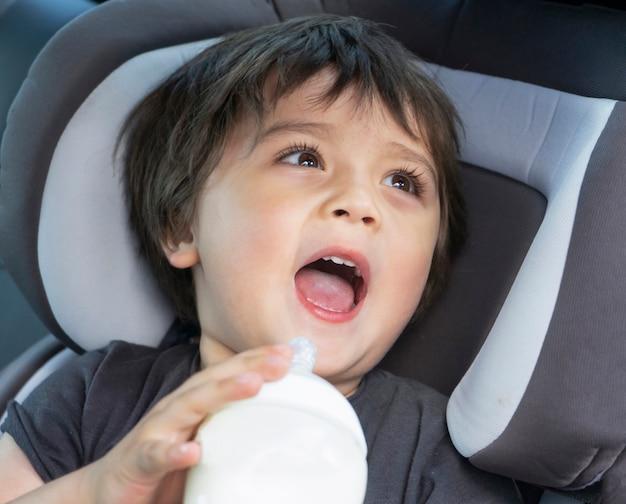 Mignon petit garçon buvant une bouteille de lait dans un siège de voiture pendant un voyage Photo Premium
