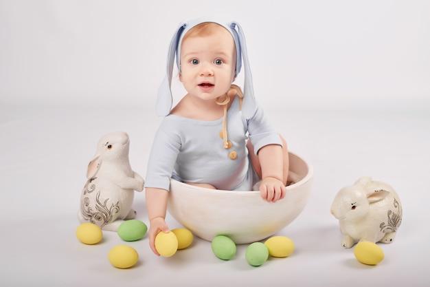 Mignon Petit Garçon Drôle Avec Des Oreilles De Lapin Et Des Oeufs De Pâques Colorés Et Des Lapins. Bébé De Pâques. Modèle De Carte De Voeux De Pâques. Photo Premium