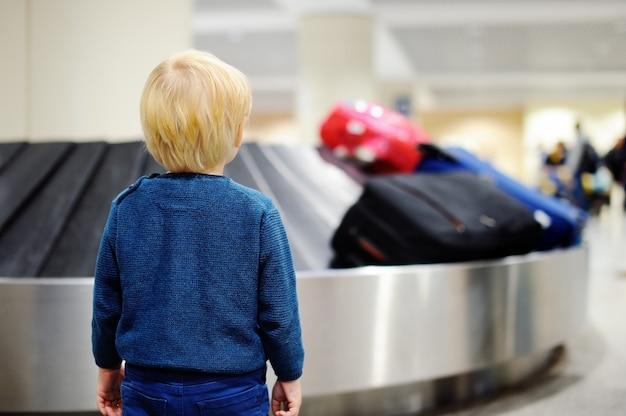 Mignon petit garçon fatigué à l'aéroport, en voyage. contrarié enfant en attente avec valise pour enfants sur le carrousel à bagages. Photo Premium