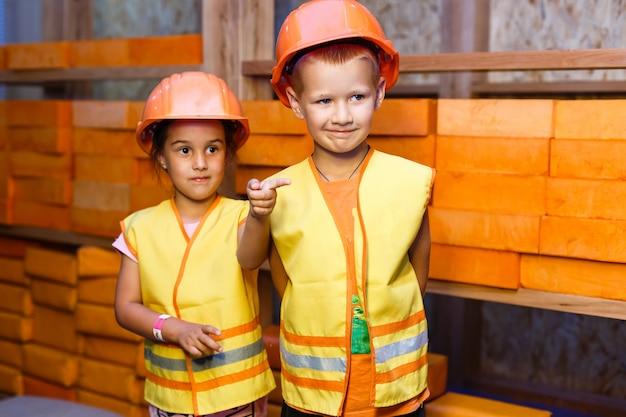 Mignon petit garçon et fille jouant avec des outils de jouet et souriant à la caméra Photo Premium