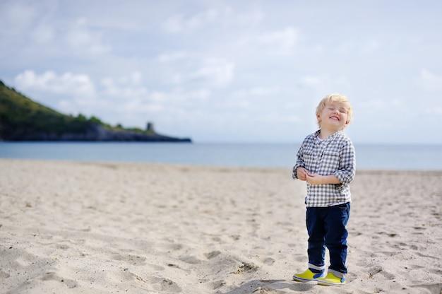 Mignon petit garçon heureux profiter de vacances sur la plage près de la mer tyrrhénienne. drôle enfant mignon faisant des vacances et profiter de l'été. Photo Premium