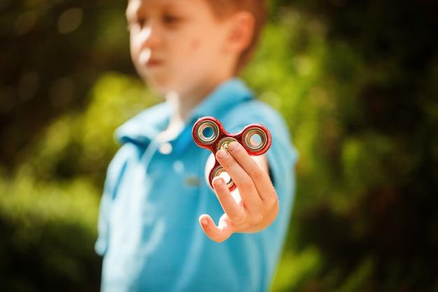 Mignon petit garçon jouant avec le fileur de main fidget en jour d'été. jouet populaire et tendance pour enfants et adultes. Photo Premium