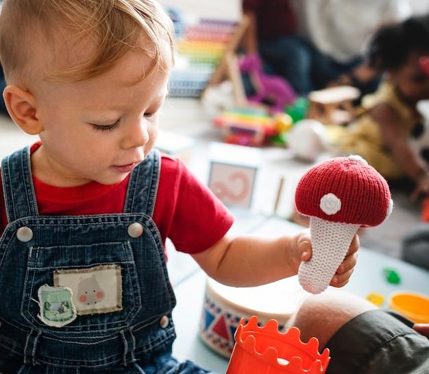 Mignon petit garçon jouant avec des jouets au centre d'apprentissage Photo Premium