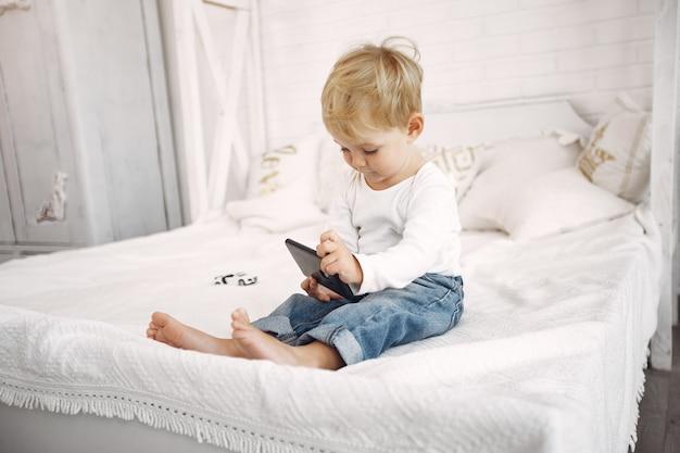 Mignon petit garçon jouant avec un ordinateur portable sur un lit Photo gratuit