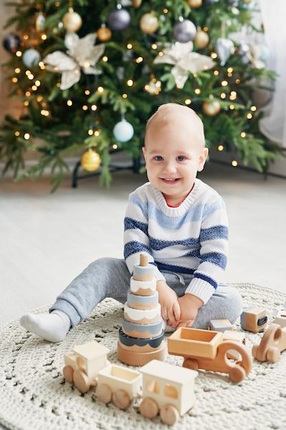 Mignon petit garçon joue avec train en bois jouet, voiture jouet, pyramide et cubes, concept de développement d'apprentissage. développement de la motricité fine des enfants, de l'imagination et de la pensée logique Photo Premium