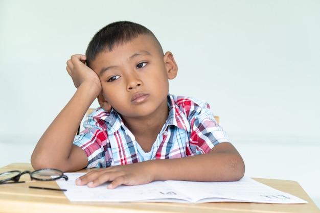 Mignon petit garçon ne fait pas ses devoirs Photo Premium
