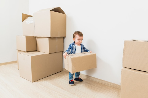 Mignon petit garçon portant des boîtes en carton à la nouvelle maison Photo gratuit