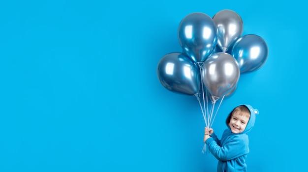 Mignon Petit Garçon Souriant Posant Avec Des Ballons à Air Isolés Sur Fond Bleu. Concept De Célébration D'anniversaire Pour Enfants. Bannière De Joyeux Anniversaire Photo Premium
