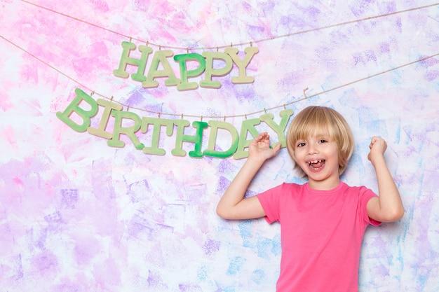 Mignon Petit Garçon En T-shirt Rose Décorant Un Mur Coloré Avec Des Mots De Joyeux Anniversaire Photo gratuit