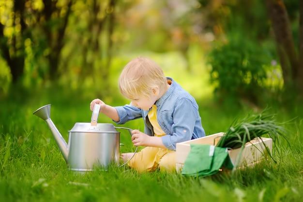 Mignon petit garçon tenant l'arrosoir dans le jardin domestique à la journée d'été Photo Premium