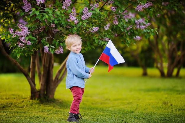 Mignon petit garçon tenant le drapeau russe. les enfants en russie. concept d'élection ou de fête nationale. fédération russe Photo Premium