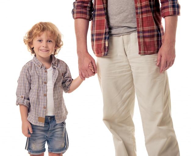 Mignon petit garçon tient sa main de grand-père. Photo Premium