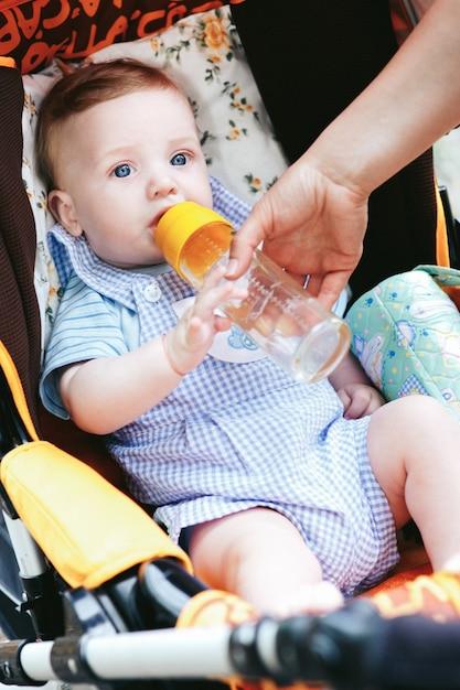 Mignon petit yeux bleus bébé garçon avec une bouteille dans la poussette Photo gratuit