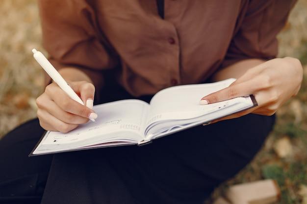 Mignonne étudiante travaillant dans un parc et utilisant le cahier Photo gratuit