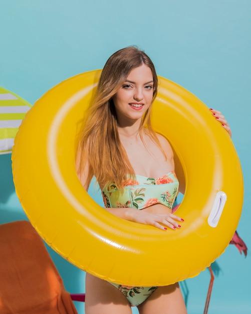 Mignonne jeune femme debout dans un cercle de nage en studio Photo gratuit