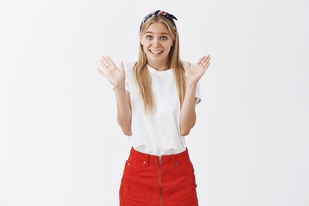 Mignonne Jeune Fille Blonde Maladroite Posant Contre Le Mur Blanc Photo gratuit