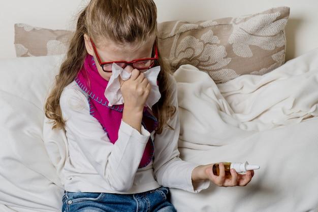 Mignonne jeune fille enfant dans des verres à éternuer dans le soufflage de tissu Photo Premium