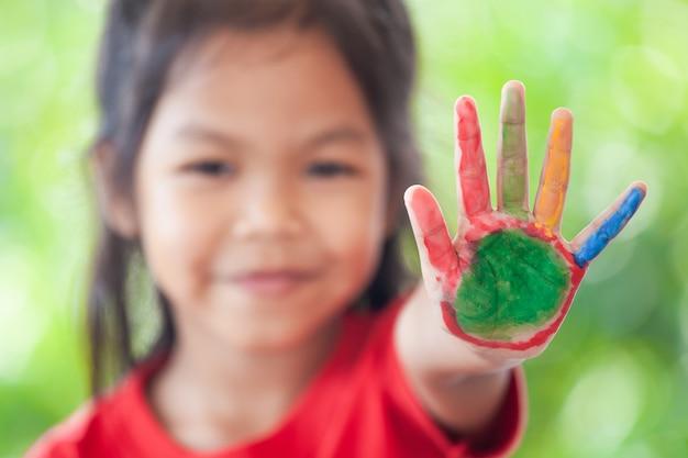 Mignonne Petite Fille Asiatique Avec Des Mains Peintes Montrant Le Nombre De Doigts Cinq Photo Premium