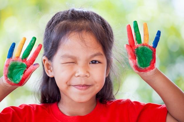 Mignonne petite fille asiatique avec des mains peintes souriant avec plaisir et bonheur Photo Premium
