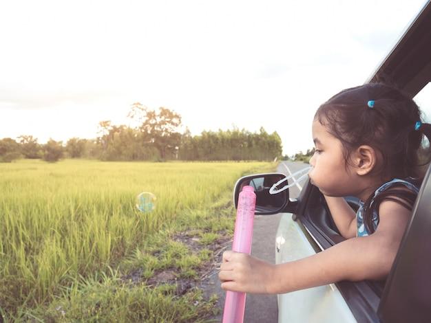 Mignonne petite fille asiatique soufflant des bulles par la fenêtre de la voiture et s'amusant à voyager en voiture Photo Premium