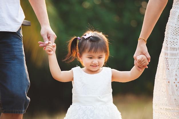 Mignonne petite fille asiatique tenant la main et marchant avec ses parents dans le parc Photo Premium