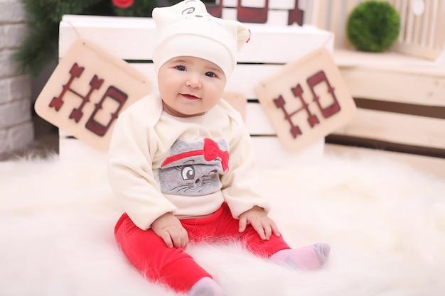 Mignonne Petite Fille Assise Sous L'arbre De Noël Dans La Chambre Photo Premium