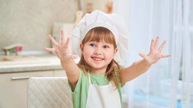 Mignonne petite fille chef montrant sa paume Photo Premium