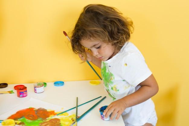 Mignonne petite fille dessinant avec des peintures colorées Photo gratuit