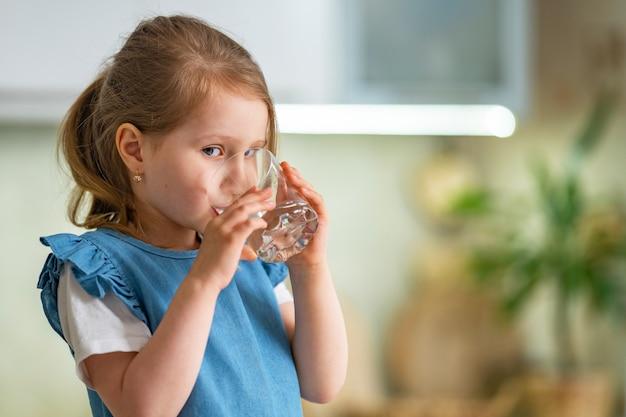 Mignonne Petite Fille De L'eau Potable Dans La Cuisine à La Maison Photo Premium