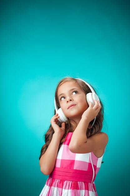La Mignonne Petite Fille Joyeuse Avec Un Casque Sur Le Mur Orange Photo gratuit