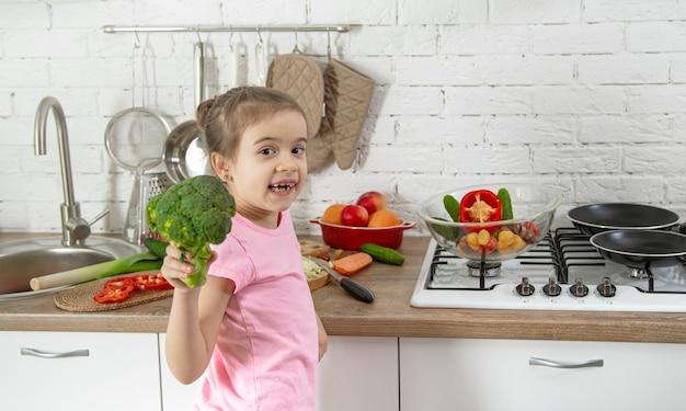 Mignonne Petite Fille Avec Des Légumes Dans La Cuisine. Le Concept D'une Alimentation Et D'un Mode De Vie Sains. Valeur Familiale. Photo gratuit