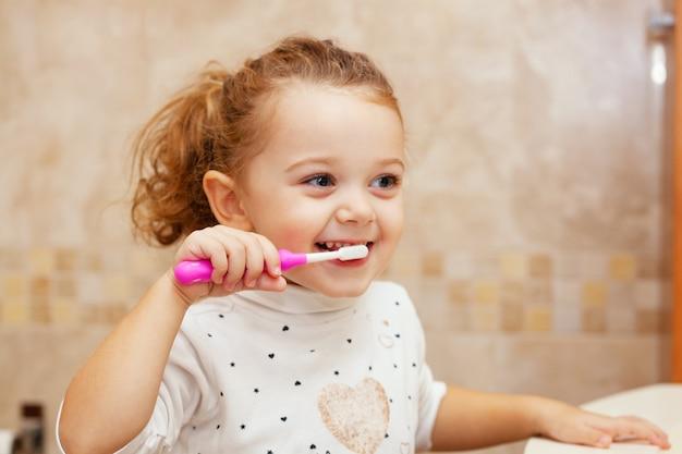 Mignonne Petite Fille, Nettoyage Des Dents Avec Une Brosse. Photo Premium