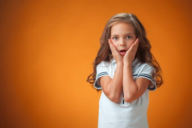 La Mignonne Petite Fille Surprise Sur Fond Orange Photo gratuit