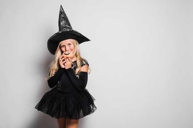Mignonne petite sorcière avec minuscule jack-o-lantern Photo gratuit